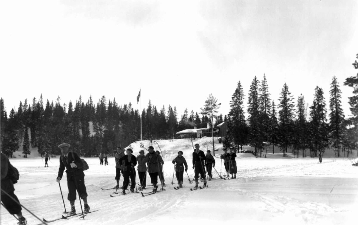 Skiløpere i Nordmarka, Oslo. 1934. Tryvannstua med flagget til topps ses i bakgrunnen.
