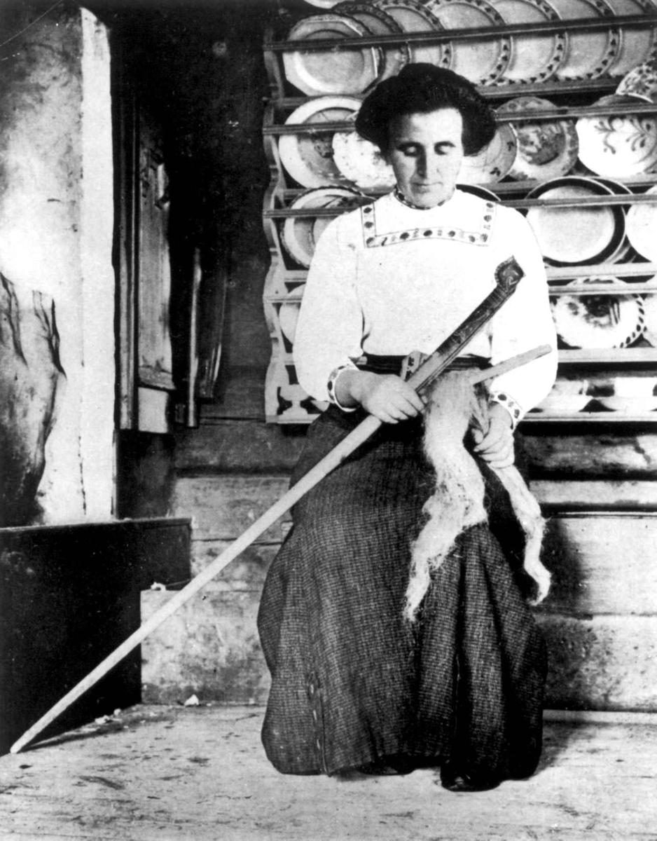 Bråking. En kvinne sitter og garmer, brekker lin med linklemme. En tallerkenhylle på veggen i bakgrunnen. Meldal, Nord-Trøndelag.