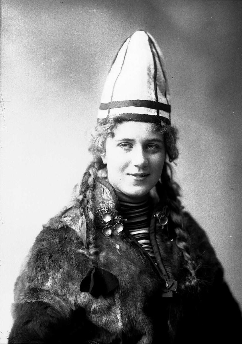 Kvinne i sameliknende drakt med pesk og lue.