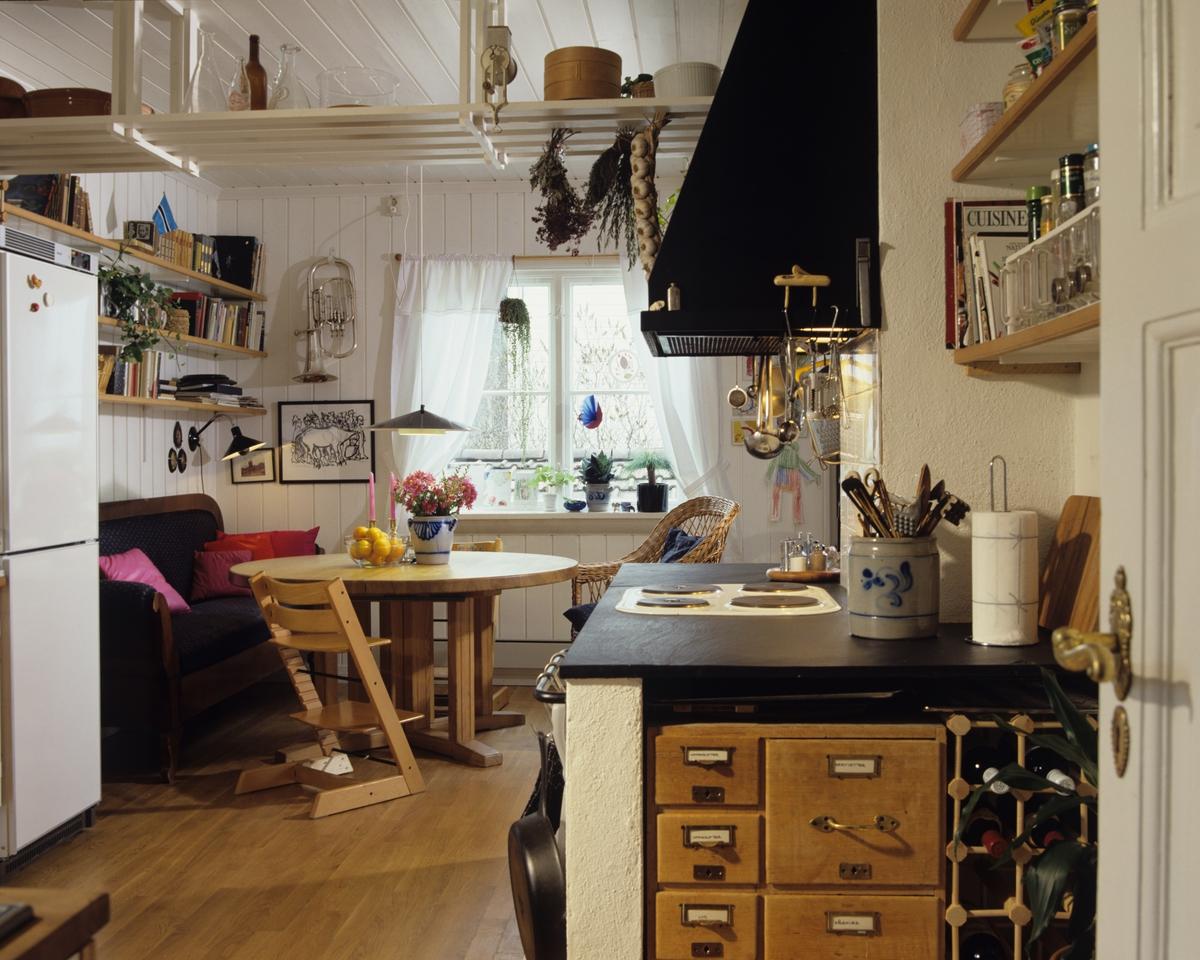 Fra kjøkkenet med kjøleskap, skuffer og komfyr, i hjørnet på stuen står en sofa og bord og en hylle som henger fra taket. llustrasjonbilde fra Bonytt 1987.
