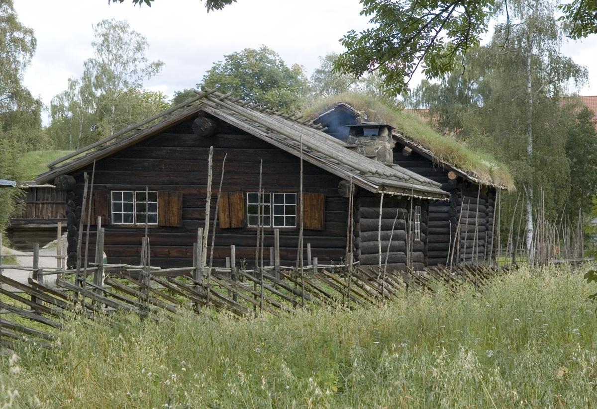 STUE FRA GRØSLI I FLESBERG, CA. 1650  Overført til museet 1895, gjenoppført 1899   Stua ble antagelig bygd av den velstående bonden Hallvard, som eide gården fra 1604 til 1653. Stua har den samme treromsplanen, med forstue, kove og stuerom, som den 350 år eldre stua fra Søre Rauland. Ildstedet er peis med røykpipe, og det antas at stua fra Grøsli var blant de første peisestuene i dalen. De eksisterende vinduene, med tresprosser, ble satt inn tidlig på 1800-tallet, mens de opprinnelige vinduene var mindre og hadde blysprosser. Det sponkledde taket er et karakteristisk trekk ved huset. Under sponkledningen ligger et vanlig torvtak.  Med peis i stuene oppsto en innredningsskikk som fulgte diagonale linjer. Senga og døra står diagonalt i forhold til hverandre. Det samme gjør peisen og høysetet med bord foran. Andre nye innredningselementer er skapene, der det midterste skjuler en seng til å slå ut. Gulvuret står mellom de to vinduene i gavlen, og vogga henger nær senga. Bordet, som kan slås opp mot veggen mellom peisen og senga, kalles i Numedal for en «skivju». På gavlveggen henger en «tavlett», ei hylle til bøker og småting. I stua finnes flere inventarstykker som skriver seg fra Fles¬berg kirke, slik som dørene til forstue og kove i renessansestil, og øverste del av senga. Likedan høysetetavla, som har vært rygg i en kirkestol, og bærer innskriften (H)ERREN-ER-NER-HOS-ALE-DEM-SOM-KALE PAA (HAM). DEN 14-SEPTEMBER-ANNO DOMNI 1633.  (Tekst hentet fra By og bygd 43, 2010)