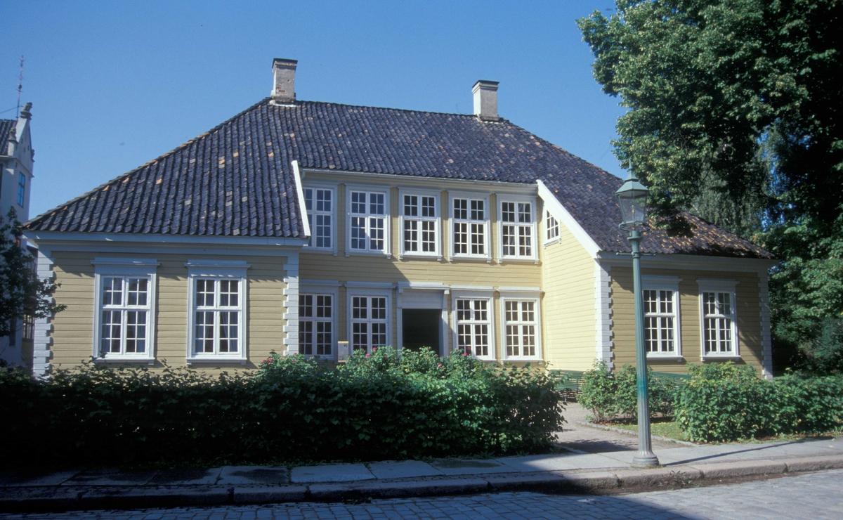 «CHRYSTIEGÅRDEN»,  BYGÅRD FRA BREVIK, 1761  Overført til museet 1916, gjenoppført 1946-71   Gården ble bygd etter at en brann hadde lagt store deler av Brevik i aske. De mange husene: hovedbygning, drenge-stue, bryggerhus, vedskur med stor kjeller og uthus med stall, fjøs, løe og låve, lå ordnet rundt et firkantet gårdsrom. Det opprinnelig rødmalte, stående panelet er fortsatt bevart mot bakgården. Panel og fargesetting på hovedfasaden er fra en ombygning i begynnelsen av 1800-årene. Fasaden vendte mot Breviks Storgate. På den andre siden av gaten lå tilhørende brygge, stor sjøbu og lastehus. I tilknytning til gården var det anlagt en urtehage.   Hovedhuset har ni rom og kjøkken. I annen etasje er det en stor sal og to mindre rom. Møbleringen er foretatt med bakgrunn i detaljerte skifte- og auksjonsprotokoller fra gården fra slutten av 1700-årene. I den grad det var mulig, ble huset fylt med gjenstander fra Brevik- og Porsgrunnsområdet i Norsk Folkemusems samlinger.   Bygningens spesielle eksteriør med to framspringende fløyer i første etasje har antagelig sitt forbilde i hovedbygningen på Borgestad herregård ved Porsgrunn fra 1690-årene, som igjen er påvirket av grev Ulrik Fredrik Gyldenløves herregård i Larvik fra 1677.   Samtiden omtalte dette som «italiensk stil». Brødrene Hans og Jørgen Chrystie oppførte hvert sitt hus i denne stilen i Brevik.   Brødrene Hans og Jørgen var sønner av skotten David Chrystie (1693-1736) som slo seg ned i Brevik i 1724. Han giftet seg med Karen Winther. Ti av deres tolv barn vokste opp. Det var deres eldste sønn, Hans Chrystie (1720-1797), som lot oppføre den herskapelige Chrystiegården i 1761. Han var kjøpmann, skipsreder og postmester og ble omtalt som en meget kultivert og dannet herre med boklige interesser. I auksjonsprotokollen etter hans død fremgår det at han etterlot seg hele 21 fuglebur. Hans Chrystie giftet seg med Dorthea Ording (1724-1778). De fikk ni barn hvorav fire vokste opp. Skiftet etter henne gir et godt bilde a