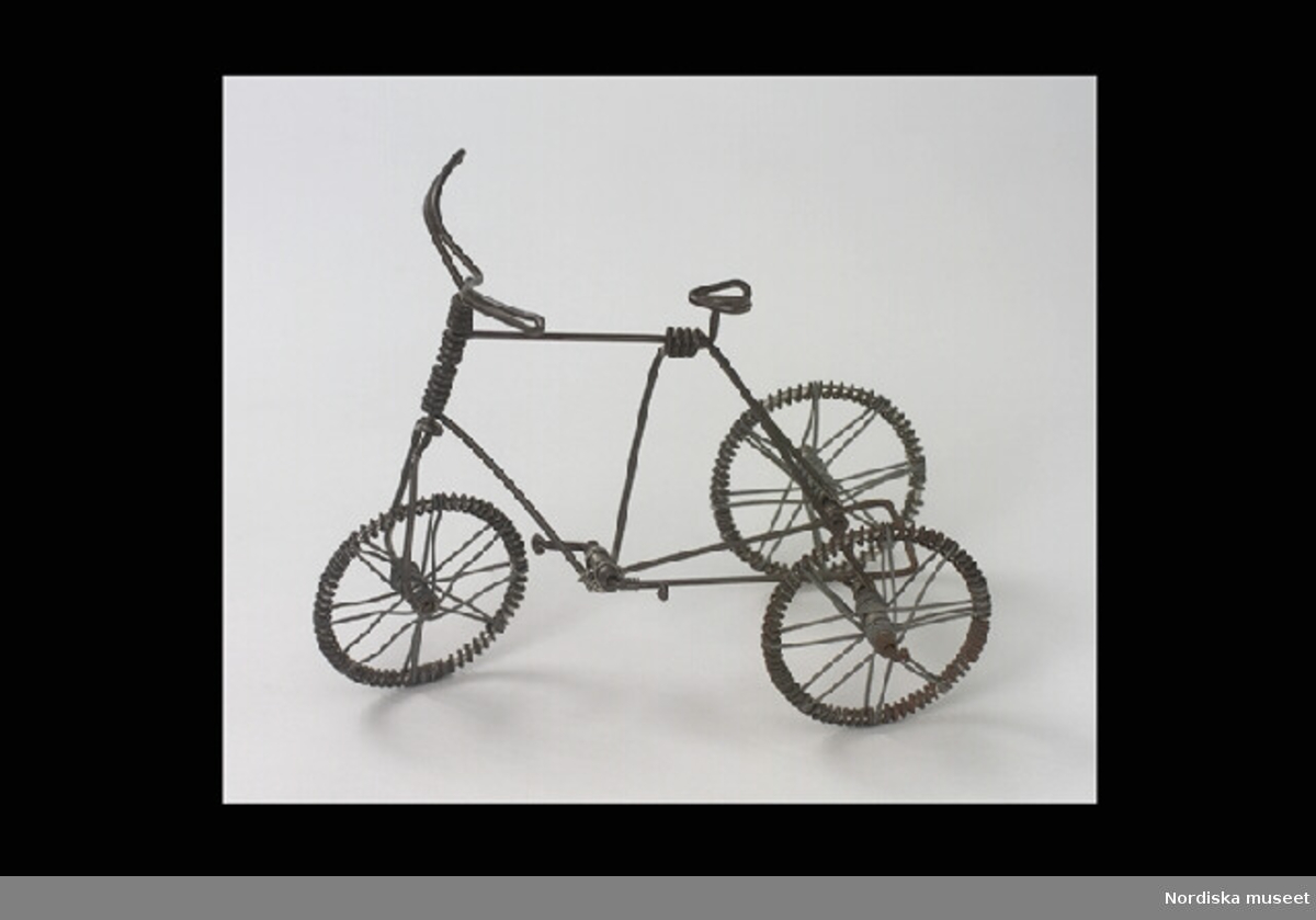Inventering Sesam 1996-1999: L 16 cm B 11 cm H 13 cm Trehjulig cykel, leksak. Helt och hållet tillverkad av ståltråd, s.k. luffararbete. Rörliga hjul och pedaler.  Inlånad till luffarutställningen 1984. Bilaga = beskrivning av luffare och luffararbeten Leif Wallin jan 1998