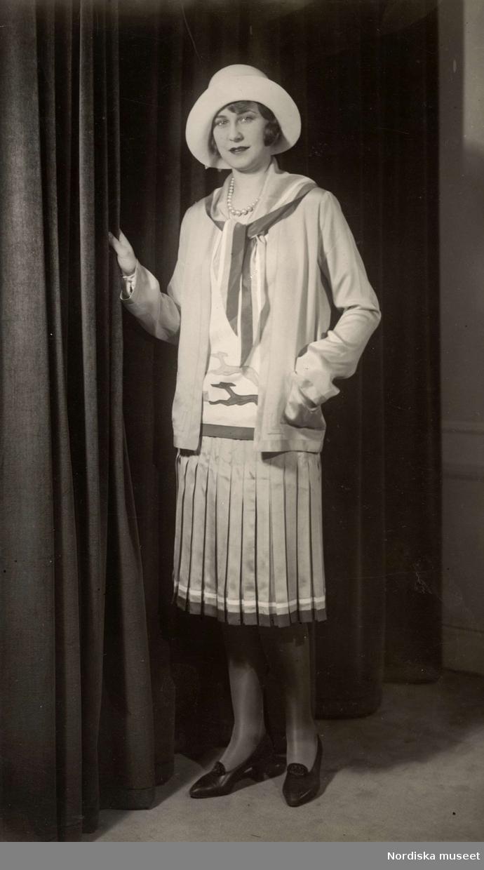 Modevisning i mars 1929. Kvinna iklädd dräkt med plisserad kjol och hatt. Nordiska Kompaniet.