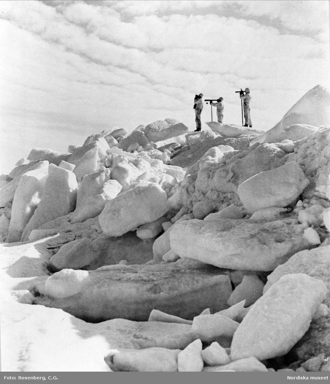 """Säljägare spanar med kikare uppe på isblock. """"I mars eller april ger sig säljägarna ut på Bottenhavet. Här har man gett sig ut på spaning efter säl."""""""