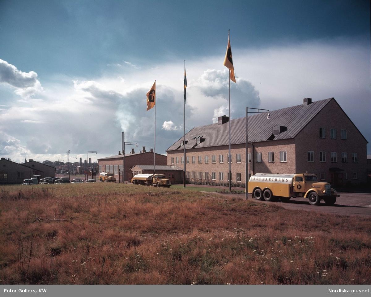 Tre tankbilar, Koppartrans, på rad med gula tegelbyggnader i bakgrunden. Göteborg.