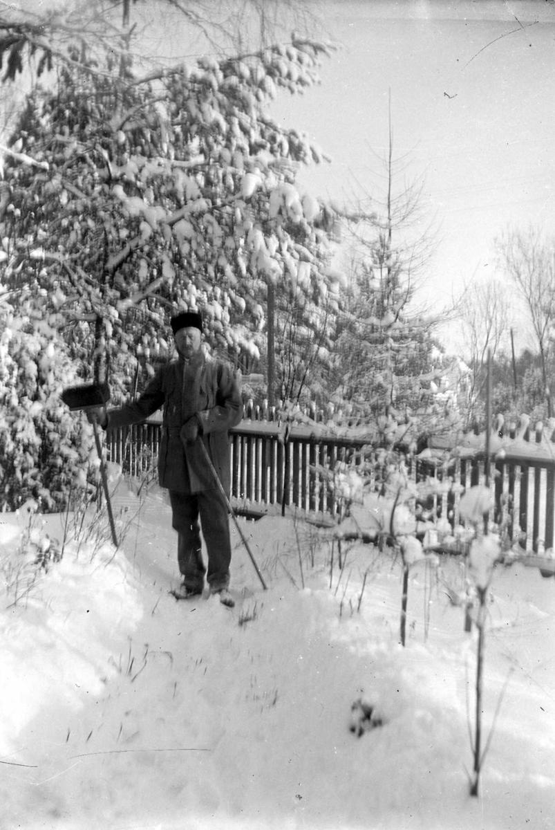 Vinterbild. Helporträtt av en man med sopborste i trädgården.