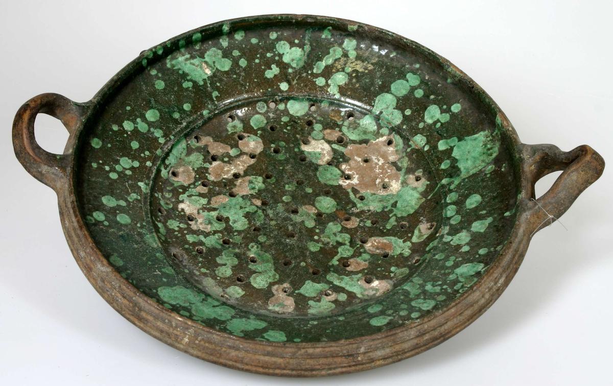 Durkslag av lergods. Grönglaserat med fläckar av piplera i ljusare grönt. Ett av handtagen hoptryckt på mitten.