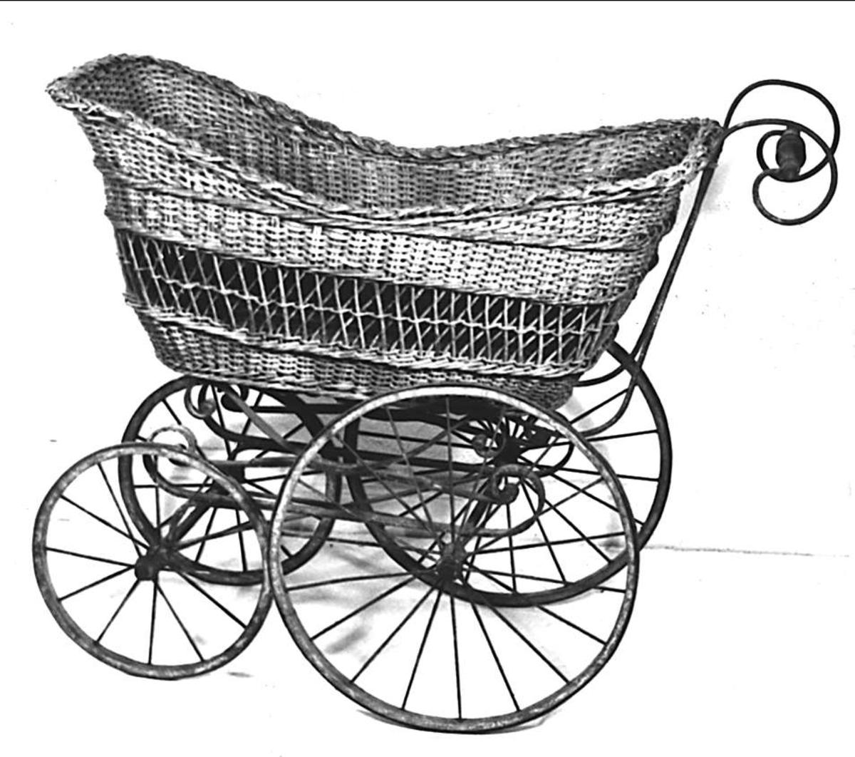 Barnvagn av flätad korg och underrede av järn. Handtag av svarvat trä. Hjulen av järnskodda träringar.