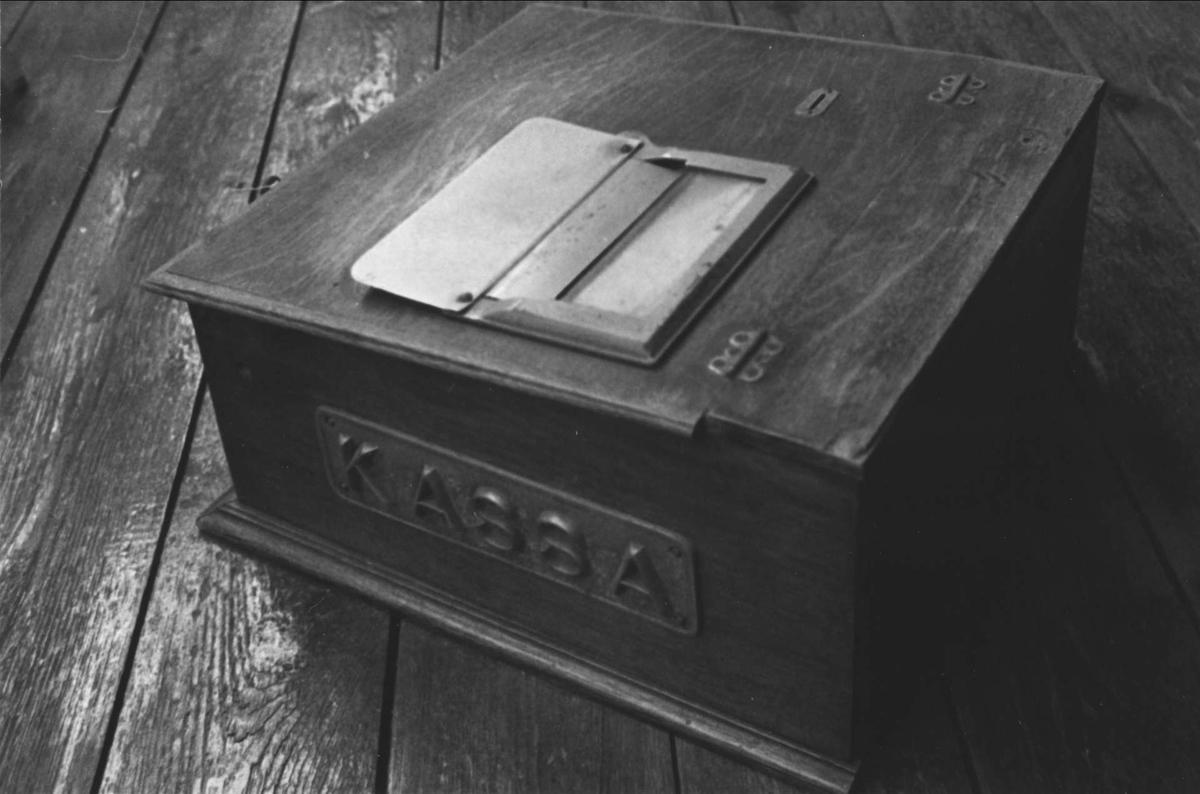 Kassapparat av trä med pulpetställt lock. Utdragbar låda för pengar, anordning för utskrivande av kvitton samt ringanordning. På kassaapparatens högra sida en gjutjärnsplatta med texten KASSA i relief.