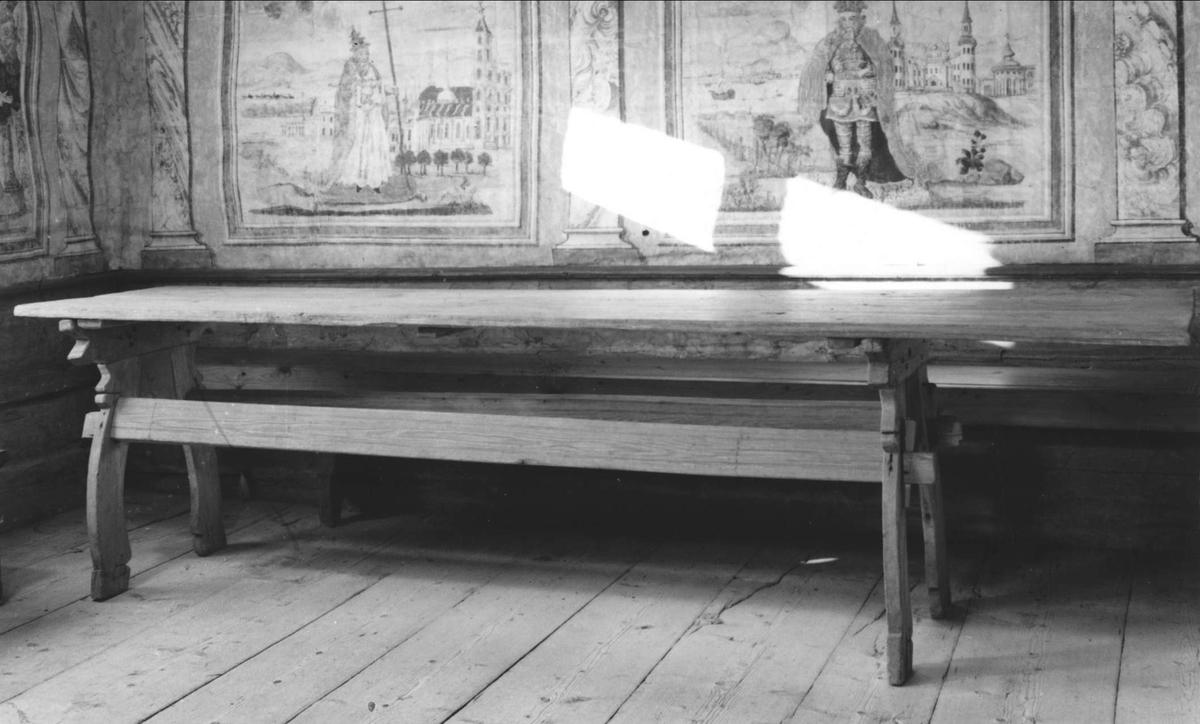 Bockbord av trä. Skivan av två plankor med narar under. Profilerade grenbensbockar med två regelbommar. På bockställen ett flertal kors inristade. Underredet kan ha varit gråmålat.