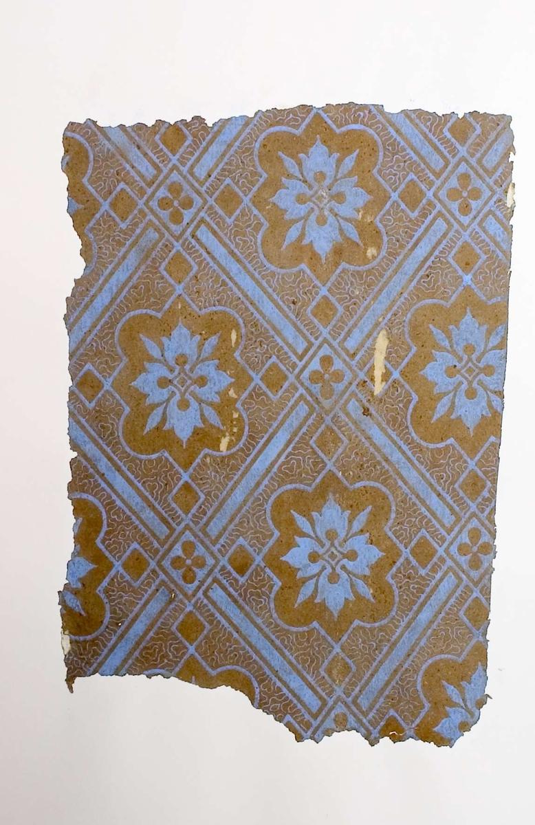 Tapetprov med tryckt mönster i ljust, blått och brunt.