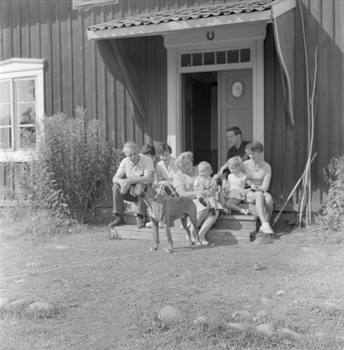 Gunnar Sundgrens familj på trappan utanför bostadshus, sannolikt Uppsala