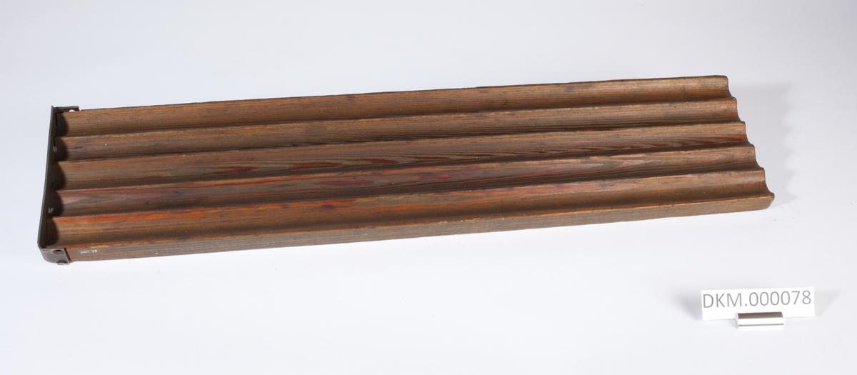 Avlang planke med fem langsgående riller. Rillene er åpne i den ene enden og stengt av ett jernbeslag i den andre enden.