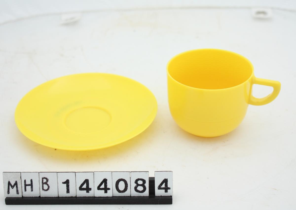 Kopp med fat. Koppen er forholdsvis lav, sirkulær og med hank. Fatet er sirkulært, og med en fordypning til kopp midt på.