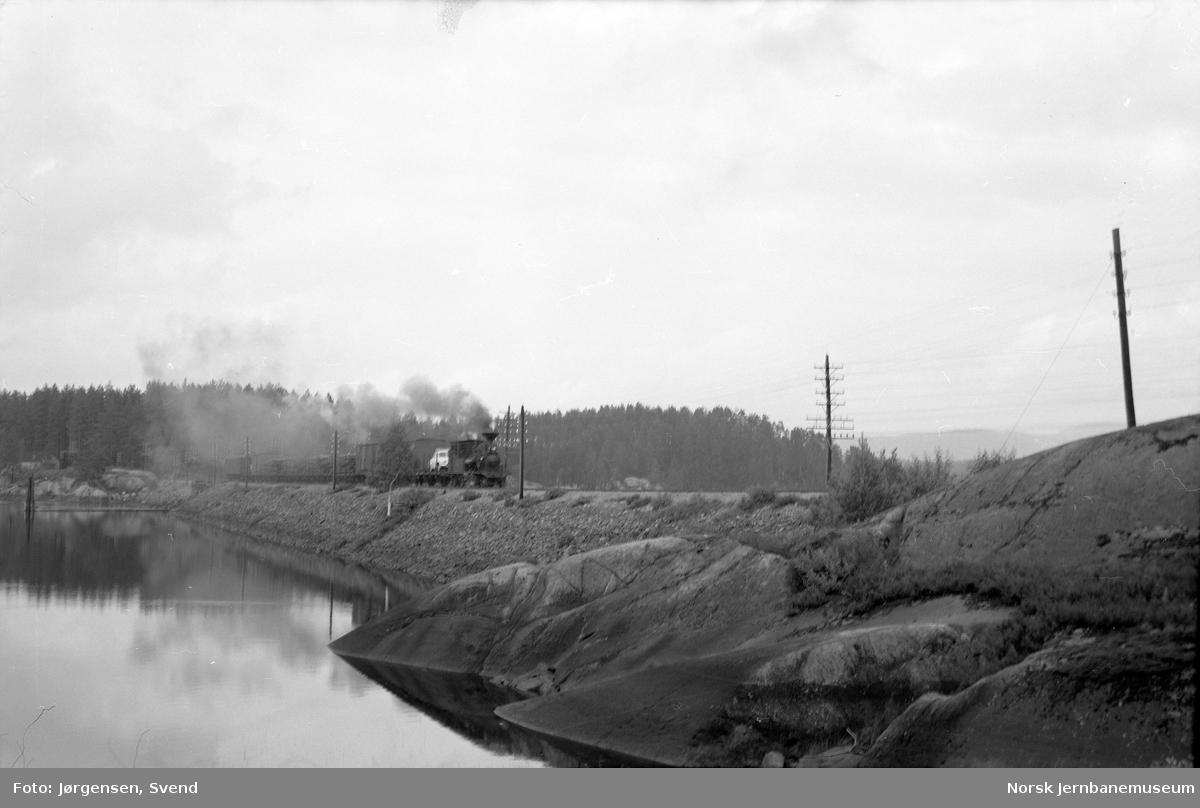 Sørgående godstog trukket av damplokomotiv på fyllingen ved Voilebukten bru