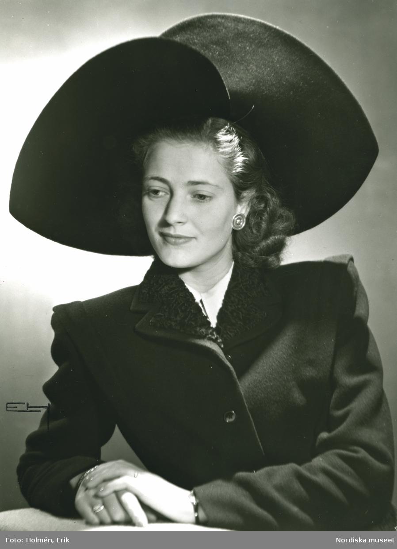 Porträtt av kvinna med bredbrättad hatt i svart filt och sammet. Hatt använd vid franska avdelningens uppvisning september 1947.