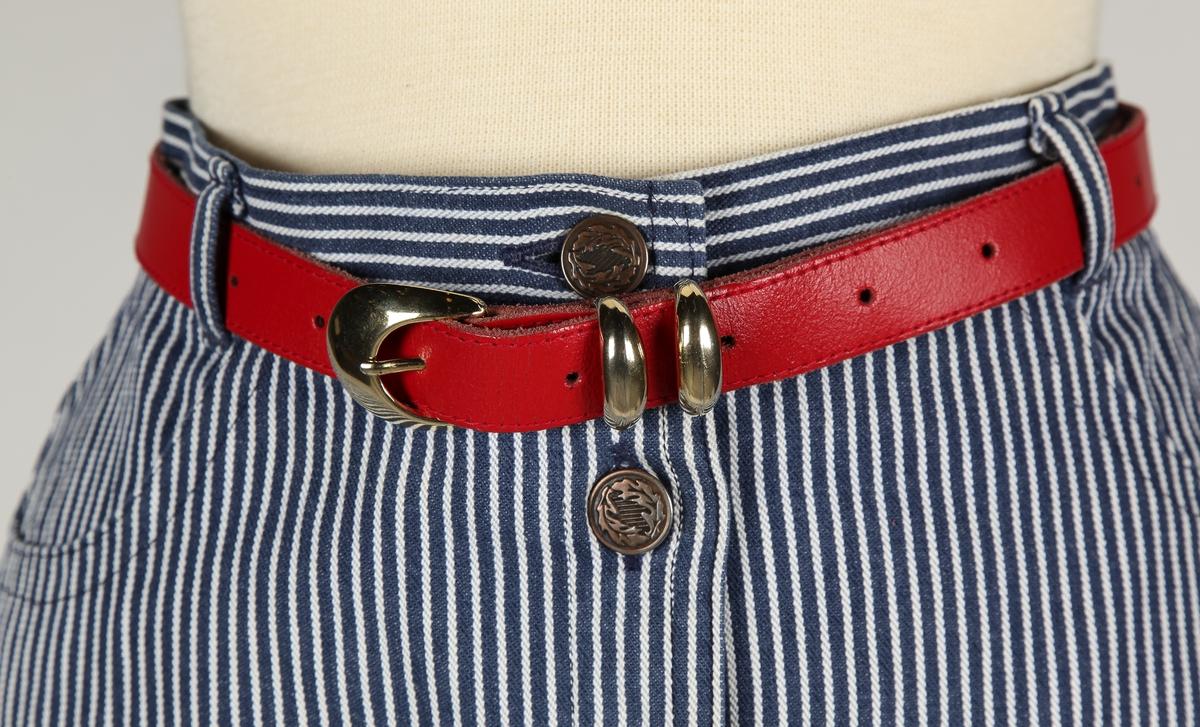 Forknappet, 7 knapper, lommer foran. Påsydde lommer bak.Fire bredder, skrådd i siden . Linning med rødt belte.  Konfeksjon.Ko-Fa  A7S 6210 Valdal.