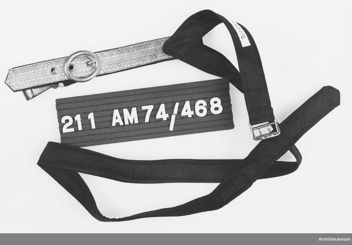 Samhörande nr är 209-38 (209-19). Sabelbärrem m/1859. Sabelbärrem i svart satin och smal guldgalon, artilleriets modell och förgyllda beslag. Livremmen av svart dubbel satin 30 mm bred och 1150 lång, sydd i spets mot bärremmen. Knäppes med byxspänne i skärpets bredd. Bäremmen i galon, 25 mm bred, 200 lång, försedd med tre stycken öljerade hål. Fodrad med mörkblått kläde. Karbinhake fäst i klädesrem, 30 mm lång 25 mm bred, mot förgyllt spänne, något ovalt. Givaren har tillverkat bärremmen själv efter egen modell.