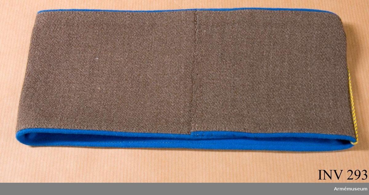 Sydd i gråbrungrön kamgarnsdiagonal med blå klädesbård, 2 mm. Hopsydd under armen med kaststygn i samma färg som tyget. Bäres på kappa.