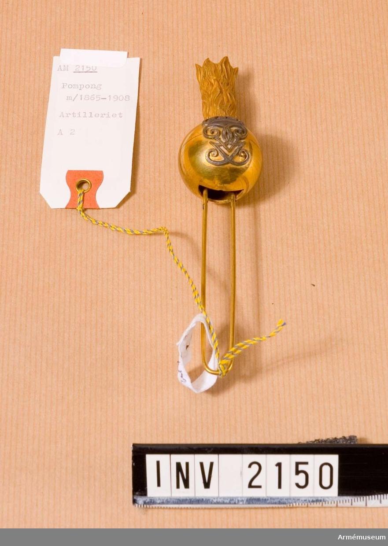 Pompong m/1865-1908 med H M Konung Gustaf V:s namnchiffer. Att bäras i käppi m/1880, mitt fram i kullen. Utförd i guld med namnchiffret i silver. Pomponghållaren stickes ned i härför avsett hål. Källa: Arméns rulla 1908.