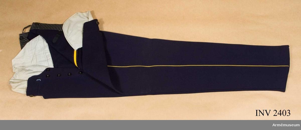 """Stl B 46. Kläde i samma färg som livplagget, mörkblå. Passpoal  av gult kläde i yttersömmarna. Byxknappar i midjan för hängsle, märkta """"Lindahl, Linköping"""". Julpknäppning. Två snedställda  fickor på framstyckena och bak en infälld ficka kantad med  svart band. Nedtill på insidan av byxbenen knappar för resår,  märkta """"Solide Elegant"""".Rulla 1908, s 275 Byxor: II Go 4 juni 1845 nr 444 och 11 nov 1872, nr 747."""