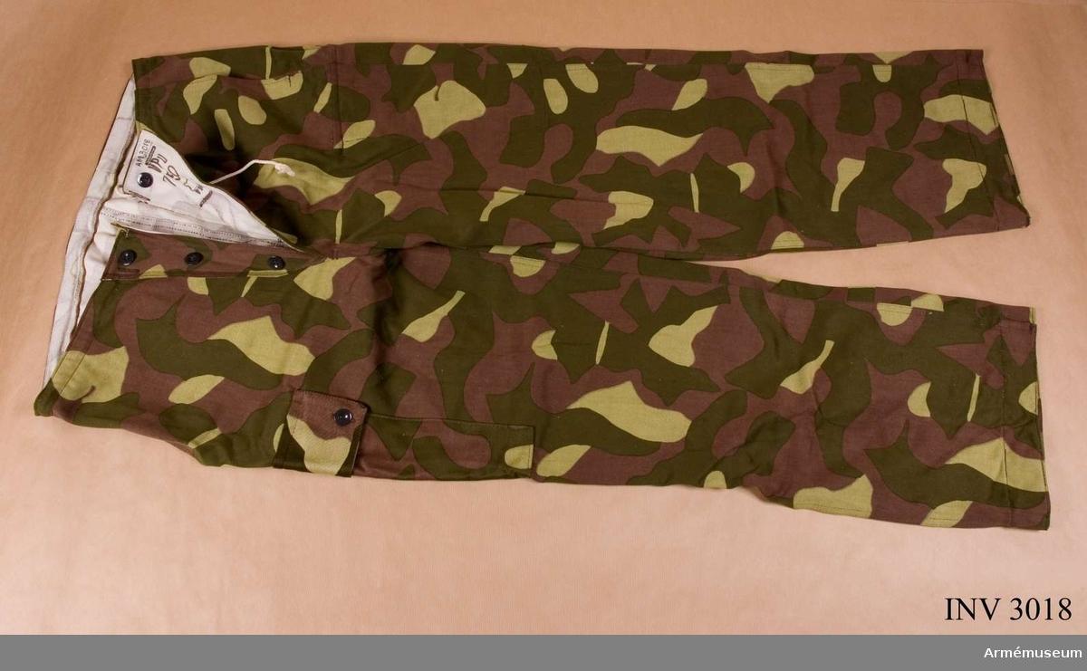 Av tyg tryckt med kamouflagefärger på vit twills med svagt genomtryck på baksidan. Användes med avigan ut som snödräkt. I midjan en tunnel med en genomdragen snodd i bomull. Knäppt mitt fram med tre knappar. Ficka med knäppt lock vid höger lårben på såväl rät- som avigsida. Märkt mitt fram på avigan. Används på sommaren som tjänstedräkt med den tryckta sidan utåt, påp vinterns över uniform m/1965 som snödräkt. Finsk gåva.
