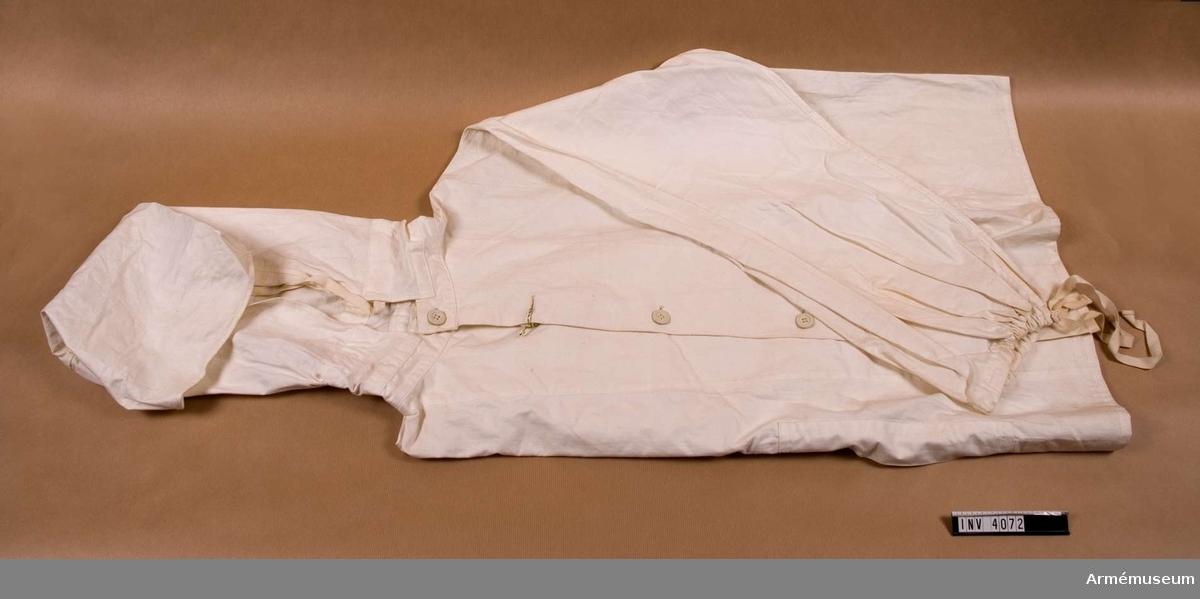 Bomull. Snöblus m/1962. Användes vintertid för kamouflage mot snön. Tyget är även vindtätt och tjänar därför som skydd mot vinden. Snöblusen har kapuschong,dragsko i halsen, knäppning fram med  fem knappar. Sprund på framstyckena för att kunna nå innerplaggets ficka. Dragsko nedtill vid ärmarna.