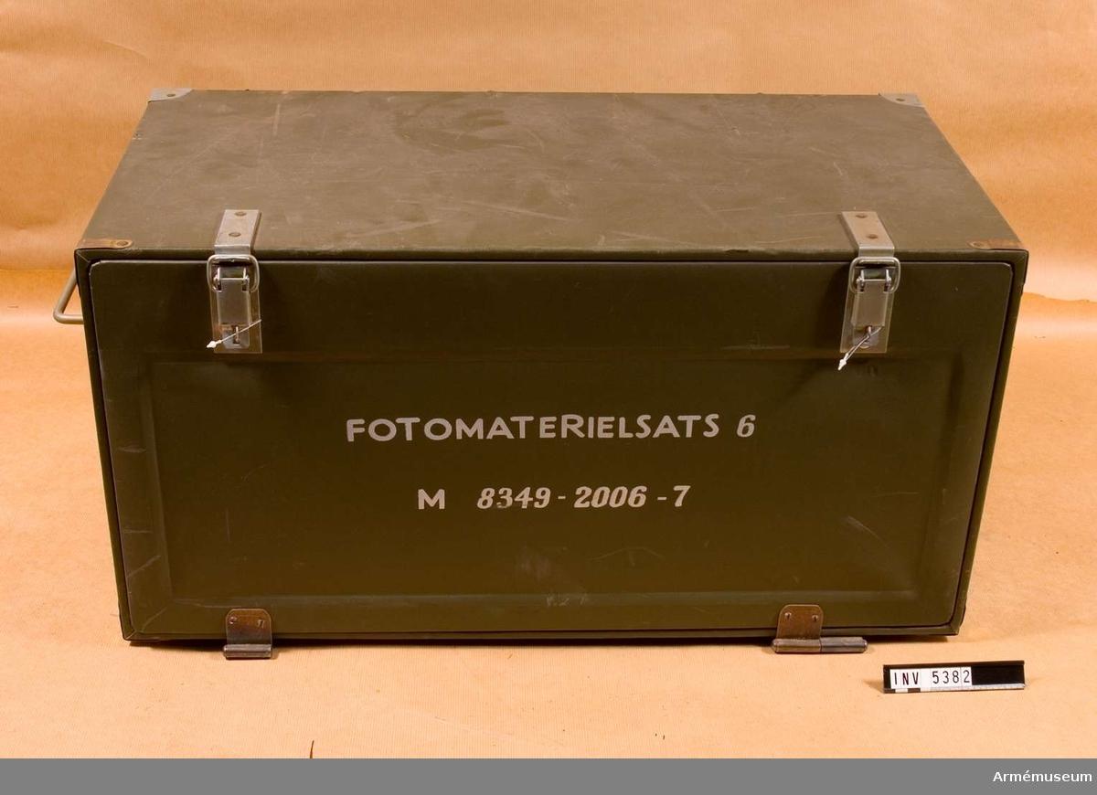 M 8349-2006-7. Fotomaterielsats 6 består av skrivpulpet med klaff, lådor för förvaring pappersvaror, optiska artiklar och skrivdon. Mått 370 x 370 x 750 mm, grön med vit text.Ena långsidan av lådan kan fällas ut och bildar då en skrivyta. Inne förvaras fyra pärmar och tre boxar, diverse block och kontorsattiraljer. Utrustningen har en del detaljer - lupp, saxar, negativkuvert och märketiketter - som tyder på att skrivplatsen är avsedd för viss administration och slutlig behandling av filmer och bilder, liksom vanligt kontorsarbete.