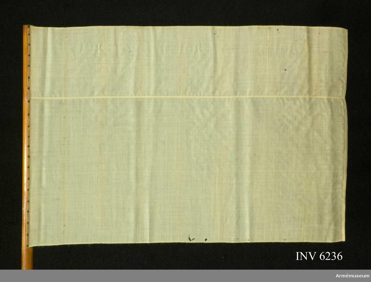 """Mått: höjd 680 mm, bredd 1000 mm, vådbredd 450 mm. Stång 1800 mm, diam 35 mm.Signalflagga, vit, fältartilleriet m/1895. Sydd av vitt  ylletyg, med vådbredden tagen en och en halv gång. På  modellappen står följande: """"Modell å Signalflagga, hvit, fastställd att tjäna till efterrättelse vid nyanskaffning för  fältartilleriet. Stockholm den 15 Maj 1895 O Svenson Generalfälttygmästare och Chef för Artilleriet"""". Stången är förnissad och nedtill skodd med järnspets för att stickas ned i marken.  Samhörande nr är 6235."""