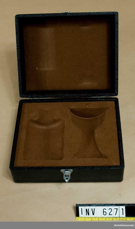 Svart etui med uppfällbart lock med spänne. Innersidan klädd med brun flanell och bottensidan  har urtag för kalk och paten. Mått 90 x 170 x 140 mm.   Samhörande nr: AM.6268-6273