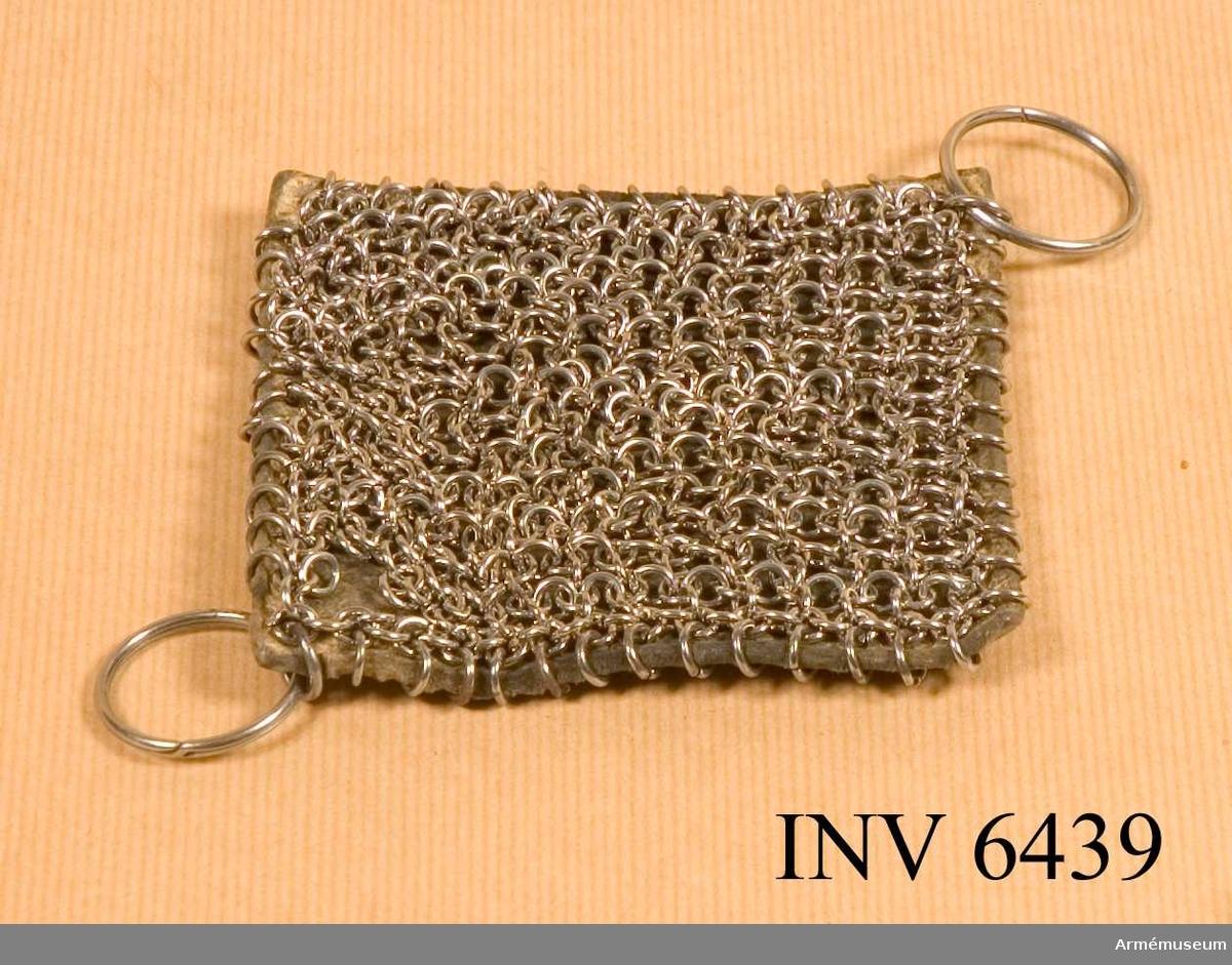 Yttersidan av kraftigt läder och fastsatt vid en brynjeplatta. Användes att putsa vapen och dylikt med.   Samhörande nr är AM.6407-6443