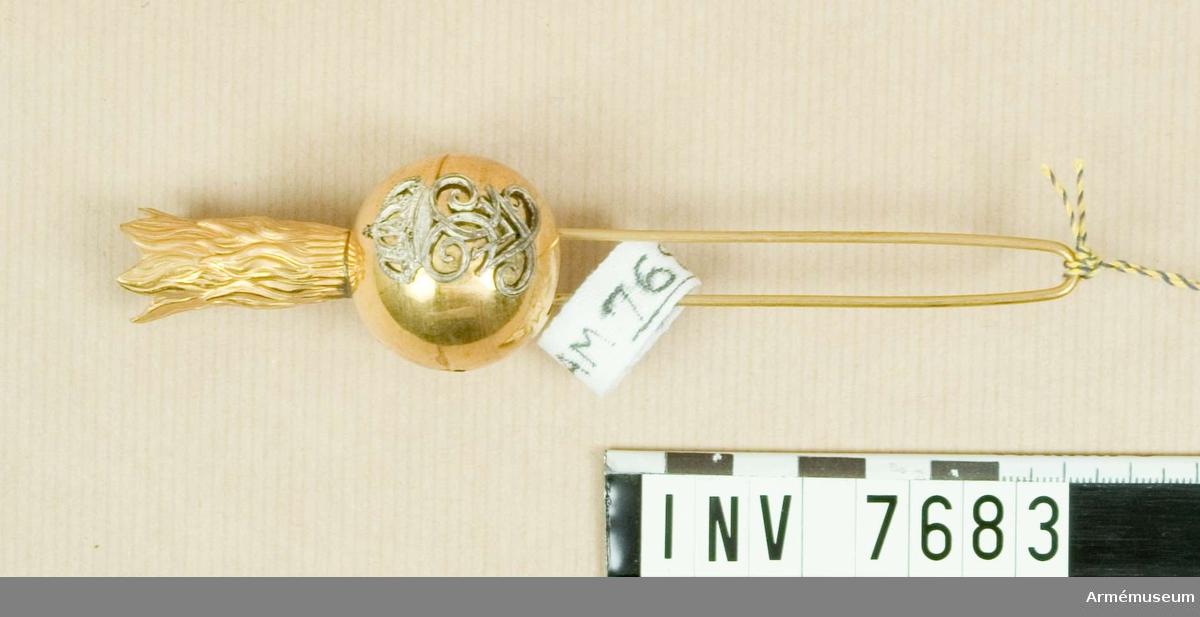 Pompong av guld med konungens Gustaf V:s namnchiffer i silver. Att bäras i käppi m/1880. Instickes upptill, mitt fram. Källa: Armens rulla 1908.