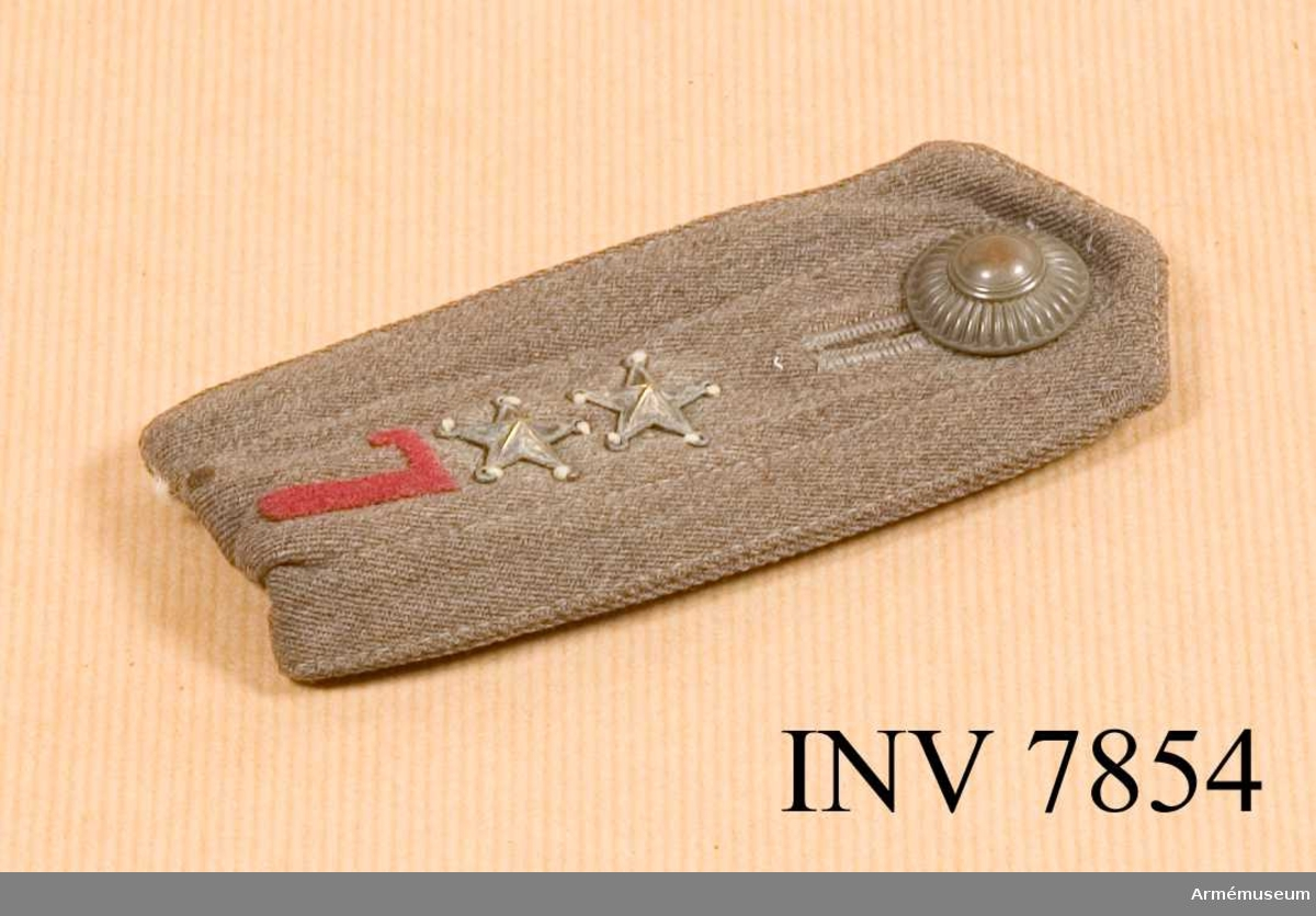 Längd 130 mm. Bredd 50 mm. Vikt 20 g. Färg gråbrungrön.  Axelklaff till kappa. Den är dubbelvikt och skall fästas under hällorna på plagget (trenchcoat och vindkavaj) och knäpps ihop med artilleriets knapp större m/1939. Axelklaffen är försedd med en röd 7:a i textil och försedd med två stjärnor av den äldre typen (med öglor att sys fast i). Betecknar grad för löjtnant.