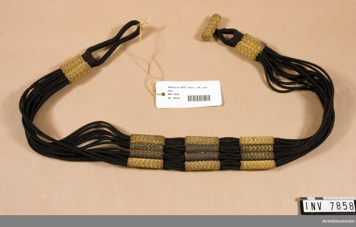Längd 850 mm. Bredd 45 mm. Vikt 120 g. Färg svart och guld.  Av svart redgarn med guldknutar. Användes till stor och liten paraddräkt.