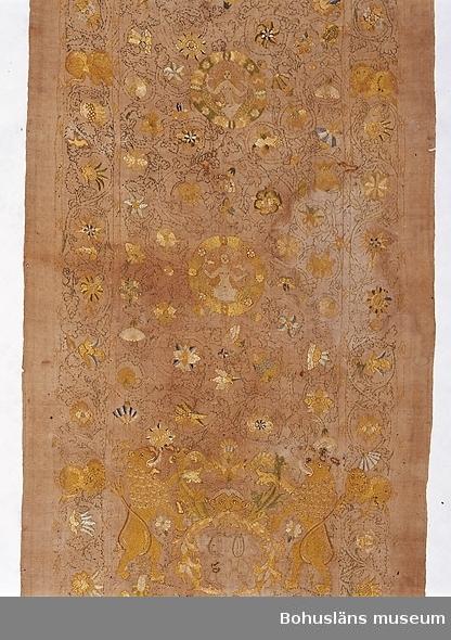 """Duken är vävd i kypertbindning; broderiet är utfört i silke av gul (dominerande), blå, ljusgrön och mörkgrön färg samt ytterst sparsamt lite i beige och vinrött, och för återgivande av smycken metallöverspunnet silke. Broderier i stjälkstygn och kedjestygn i kontursömnaden samt plattsöm och flätsöm i de ytfyllande partierna. Gåva till Uddevalla museum 1873 av Norra Ryrs församling.  Ur handskrivna katalogen 1957-1958: Dophandduk Ramens mått: 225 x 78 cm; Husaby? 1500-t. Insatt i en svart 3- delad träram, inom glas.  Litteratur: Artikel i Bohusläns Hembygdsförbunds Årsskrift 1962, """"Två broderade linnedukar från 1500-talet i Uddevalla museum"""", Åke Fredsjö, s. 17-43; artikel i Bohusläns Hembygdsförbunds Årsskrift 1963, """"Ett motstycke i Hamburg till Uddevalla museums Paris' dom-duk"""", Åke Fredsjö. Gardell, Sölve: Den kyrkliga konsten i Uddevalla museum. En vägledning för besökande, nr. 10, sidan 69. Holmberg, Axel Emanuel: Bohusläns Historisa och Beskrifning. III. Första upplagan 1845.  Kristiansson, Sten: Från Uddevalla museum. Dyrbara textilier.  Glimtar från Uddevalla museum. Ur artiklar införda i Bohus-Posten 1940-1942. Klippärm i biblioteket under Ncbk-Uddevalla."""