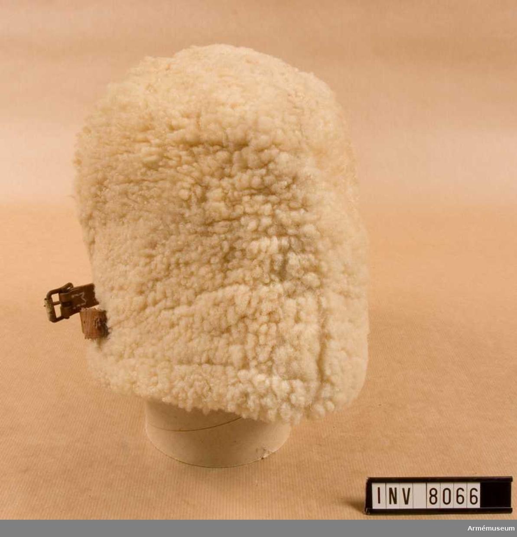 I vitt fårskinn. Höjd 170 mm. Vidd 610 mm. Vikt 300 g. Färg vit. Fodret är vadderat och har en utvikbar skärm att användas vid behov. Baktill har mössan en rem för reglering av vidden. I fodret kronmärkt Fo 51 samt I 3 1925.