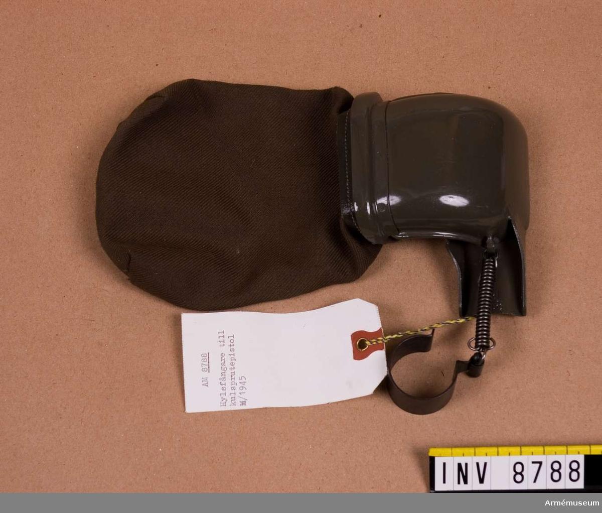 Hylsfångare t kulsprutepistol m/1945.Märkt: L & L 1958.Hylsfångare består av: Hylsavledare, klämring, fästklack och hylspåse av väv. Se Soldatinstruktion för armén Materiel 1969. sid 56-57.