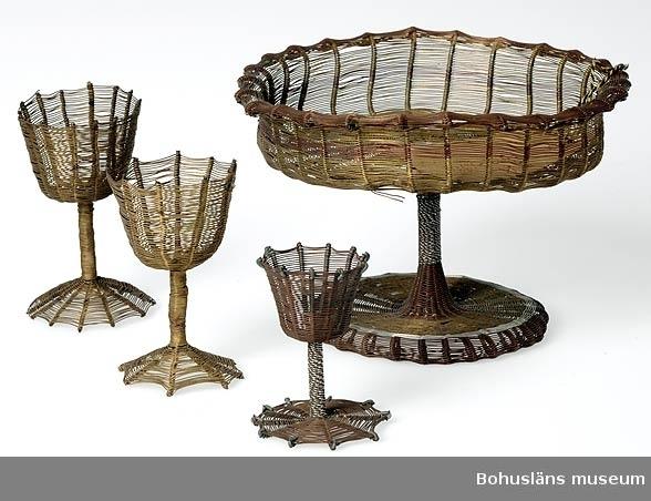 """Text till webbutställning presenterad på Bohusläns museums hemsida år 2009 - 2013 för UM001992, UM001994-UM001996: Korg (den längst till höger på bilden) från Bechuanaland; trådarbete av flera metaller bl.a. koppar och mässing. Den största korgen i samlingen är 12 cm hög. [Det gäller UM001992.] Bechuanaland var fram till år 1966 ett brittiskt protektorat i södra Afrika, numera den självständiga republiken Botswana. Föremålet är skänkt på 1920-talet av Ernst Nomell, Kimberley, Sydafrika.  Uppgifter om givaren Ernst William Nomell föddes i Uddevalla år 1861 som ett av tio barn till handlanden Johan August Nomell och hans hustru Elise Kullgren. Som ung gav han sig ut i världen som lättmatros.  I Sydafrika fick Ernst Nomell kontakt med en man som var engagerad i landets gruvnäring. Det var politikern, finansmannen och imperiebyggaren Cecil Rhodes, en man av brittisk härkomst. Nomell vann dennes förtroende, och han kom att bosätta sig i gruvstaden Kimberley, där Cecil Rhodes år 1888 medverkat i grundandet av diamantbolaget De Beer.  Den forne Uddevallabon kom att arbeta vid bolaget under många år.  Ernst Nomell var mån om att skicka gåvor till hemstadens museum.   Ur handskrivna katalogen 1957-1958: Korg av metalltråd, Betschuanaland. H. c:a 12 D. (upptill) c:a 17 cm.  på hög fot; tråd av koppar, mässing och aluminium. Hel.  Lappkatalog: 9  Enligt text på äldre museietikett: """"Gåva av Ingenior E. W. Nomell, Kimberly, Sydafrika. Ljusstakar, skålar m.m. utförda av infödingar från Betshuanaland."""""""
