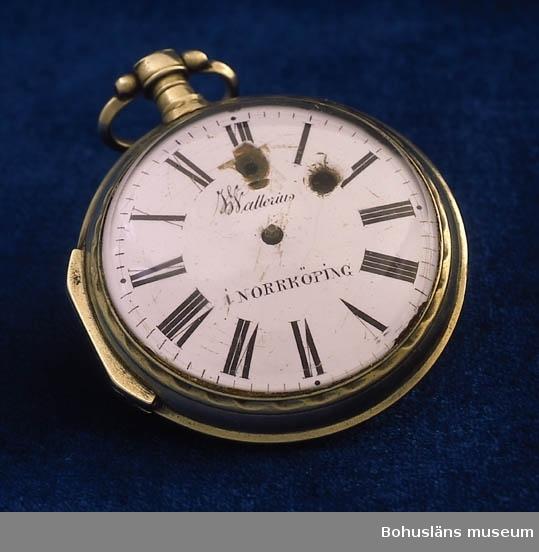 """Slät, odekorerad silverboett, bygel. Urtavla av vit emalj med svarta romerska siffror. Båda visarna saknas. I urtavlan uppdragningshål samt skada (bit ur emaljen under siffra XII). Glaset löst, kupig form med slipad konkav yta i mitten; nyckel saknas. På urtavlan märkt: """"Wallerius i Norrköping"""". Fickuret är en förfalskning från 1700-talet. Under 1700-talets andra hälft tillverkades av urmakare i Geneve med omnejd ett mycket stort antal spindelur av kraftigt sekunda kvalitet. Dessa försågs med signaturer för urmakare runt om i olika europeiska länder bl.a. signaturen """"Wallerius i Norrköping """". Någon sådan har aldrig existerat, dessa falska signaturer var ofta felstavade. Troligen har man avsett urmakaren Erik Wellenius f.1731 d. 1802; konstgjutare, urmakare och urfabrikör i Norrköping. Se Pipping, Gunnar m.fl., Urmakare och klockor i Sverige och Finland, Stockholm 1995, s. 165 och 488.  Se även UM58.8.2  Ur handskrivna katalogen 1957-1958: Fickur, silver; Wallerius, Norrköping. D. 6,3 cm.  verket trasigt, urtavlan och visarna lösa;  på baksidan av verket: """"Wallerius Norrköping"""", """"950"""".  Lappkatalog: 57"""