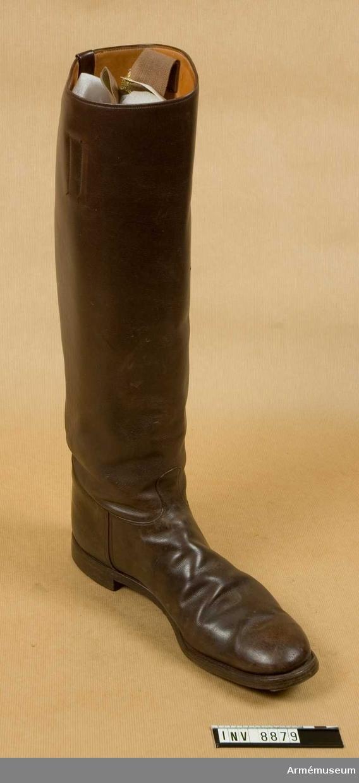 Stövlar med höga skaft att bäras utanpå byxbenet. Hankar i sidorna för hjälp vid pådragningen. Stöveln är helfodrad med läder. Detta bär stämpeln MEA. Storlek 44.
