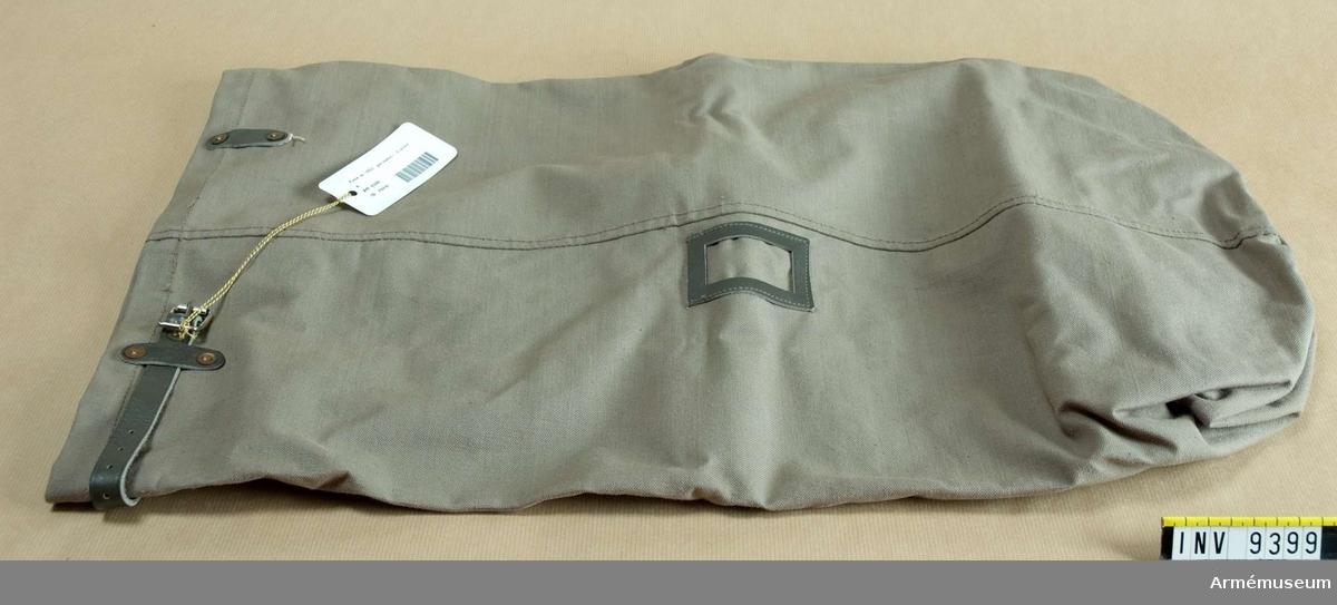 Av grå smärting, med rund botten och åtdragsrem upptill. En bärrem längs med längden av textilband, cord.