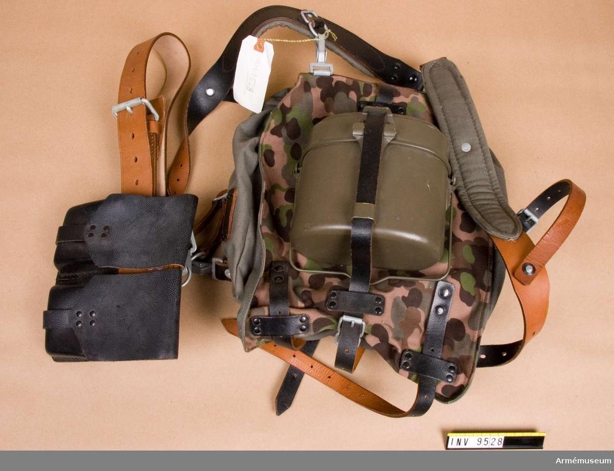 Består av ryggsäck med lock av camouflagetryckt tyg, på vilken sitter fäst med läderrem ett kokkärl. I det ljusbruna läderbältet sitter en svart läderväska. Axelremmarna är vadderade. Gåva från FMV i Solna.