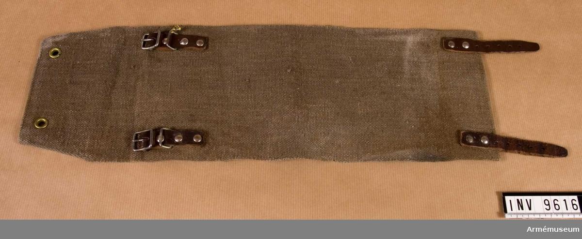 Damask m/1939.Tillverkad av gråbrungrön kanvas, ett grovt bomullstyg. Damasken knäpps med två läderremar. Den ena kortsidan  är förstärkt med läder och den andra med läder vari slagits två öljetterade hål. Har kronstämpel. Damasken tjänar som snölås mellan byxan och kängskaftet. Denna typ av snölås bars även på den civila skidbyxan av både kvinnor och män vid denna tid. Gåva från kapten Hilding Lekman.  Samhörande nr är 9605-9650 + 9659-9666. I par 9615-9616.