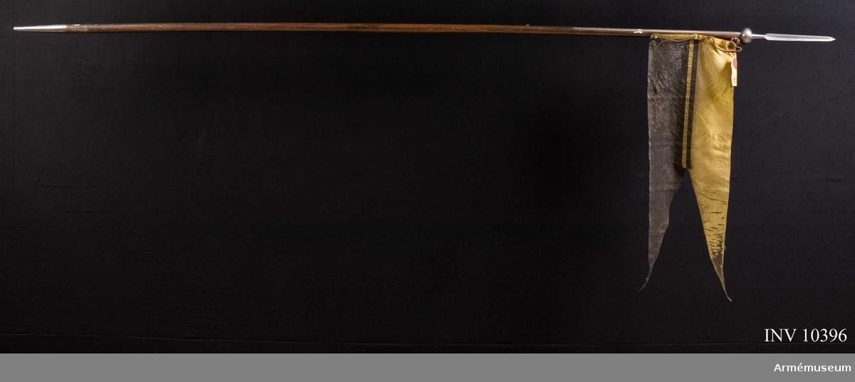 """Grupp B I.  Flagga av siden, tvåtungad, upptill längs bakre kanten förstärkt med dubbelt tyg och har i detta förstärkta parti tre hål för de ovan omtalade järnöglorna. Den fasthålles av en genom dessa tre öglor dragen svart rem. På en vid flaggan fäst lapp finns ett stort österrikiskt sigill i rött lack och påskriften: """"Muster eines Uhlanen Lanzenfähnleins nach Vorschrift vom Jahr 1828"""". Flaggans svarta parti är rätt starkt skadat. Det andra partiet är gult. Det svarta partiet skall fästas överst. Spjutbladets längd 22 cm och största bredd 2,7 cm. Doppskons längd 1,3 cm."""