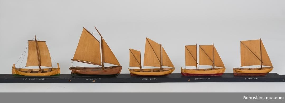 """594 Landskap BOHUSLÄN 503 Kön MAN 394 Landskap BOHUSLÄN  Fem stycken båtar fastsatta i en rad på en blåmålad bräda. Båtarna har segel av trä. Under båtarna på brädans ena långsida står namnet på båttypen: """"NORSK-NORDLANDSBÅT, ROSLAGSSKUTA, WÄTTER-SNIPA, GOTLANDS-SNIPA, BLEKINGSEKA"""".  Ur handskrivna katalogen 1957-1958: Fem modeller på segelbåtar Norsk Nordlandsbåt, Roslagsskuta, Wättersnipa, Gotlandssnipa, Blekingseka, Modeller på platta: 152 x 5,5, en båt obetydligt skadad. Från kapten Olssons saml., Fiskebäckskil.  För ytterligare information om förvärvet, se UM5087."""