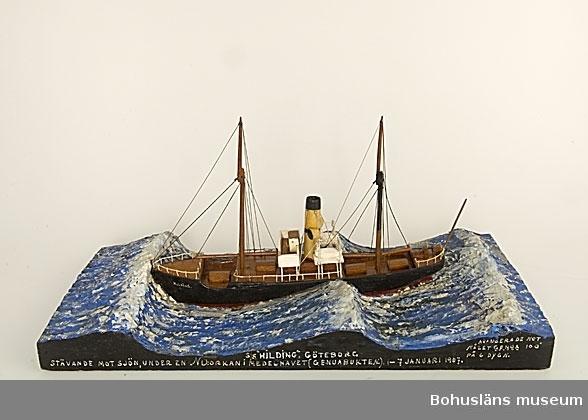 """Fartyget """"Hilding"""" monterad på en rektangulär träplatta med modellerat hav. Text på ena långsidan: S/S """"HILDING"""". GÖTEBORG STÄVANDE MOT SJÖN, UNDER EN NO:ORKAN I MEDELHAVET (GENUABUKTEN.) 1-7 JANUARI 1907. AVANSERADE MOT MÅLET GENUA PÅ 6 DYGN Historik se UM 5807.  Ur handskrivna katalogen 1957-1958: """"SS Hilding"""" Modell på platta. L. (från för till akter) 32. Föremålet helt. Från kapten Olssons saml., Fiskebäckskil.  John Emil Olsson var mönstrad på s/s Hilding med hemmahamn Göteborg som 2dre styrman 1 januari - 26 augusti 1907 för resa  Dunkerque England till Medelhavshamnar, Norge m fl platser och tillbaka till  Grimsby, som 1ste styrman 26 april1907 - 12 januari 1908 på resa från Grimsby - Norge till England, Halland mfl. platser och tillbaka till Göteborg, som 1ste styrman 19 mars - 21 september 1908 från Göteborg till utrikes orter och tillbaka till Göteborg.  För ytterligare information om John Emil Olsson och förvärvet, se UM005807.  Föremålet presenterat på Bohusläns museums hemsida år 2009 - 2013, webbutställning """"John Emil Olsson Fiskebäckskils sjöfartsmuseum""""."""