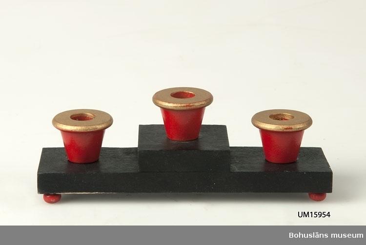 Svartbetsad platta, högre mitt. Tre röda koniska ljushållare för julgransljus med guldfärgad kant, fyra små röda kulfötter.  Se UM015810
