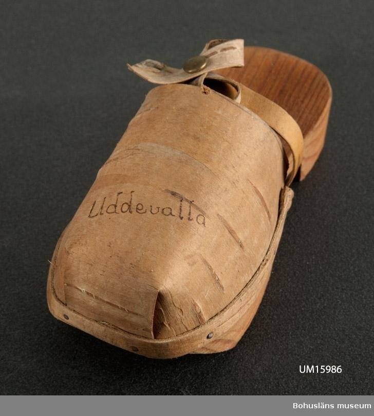 """Botten av trä, ovandel av näver med ordet """"Uddevalla"""" på. Troligen tillverkad på 1950-talet.  Se UM015810"""