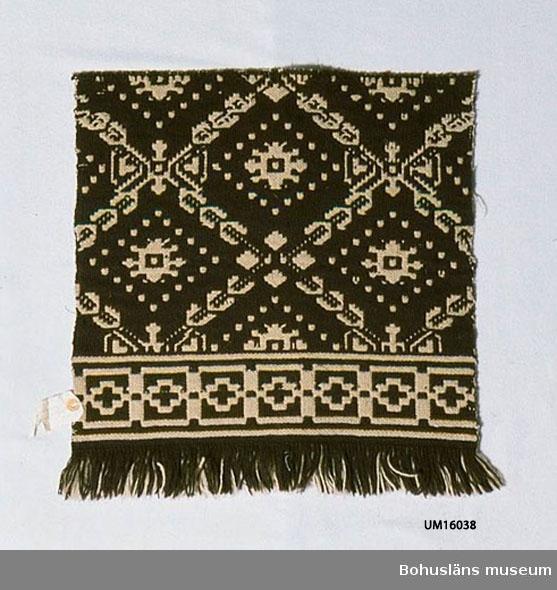 """433 Teknik 1 FINNVÄV; MÖNSTRAD DUBBELVÄV 412 Förvärvstillst VÄLBEVARAD Rekonstruktion av UM 16044 som är ett vävnadsfragment av en tidig finnväv (troligen 1800-talets första hälft) från Lilla Resby, Hålta, Inland. Se även UM 2240 med liknande mönster. Av brunt och mycket ljust gråbeige tretrådigt ullgarn. Har bård med geometriskt mönster nertill. Ovanför bården mönstrad  med diagonalrutor uppbyggda av stiliserade små blad. Inuti varje ruta en stiliserad blomma omgiven av små rutor som bildar en romb runt  blomman. Nertill oknutna fransar av varpen. Langettstygn sydda runt överkanten för att tyget inte ska repas upp.  På etikett fäst vid kanten står på ena sidan: """"Tillhör Gbgs och Bohusläns hemslöjdsförening"""". På andra sidan: """"Finnväv Provvävnad 27"""".  För ytterligare uppgifter om givaren se UM016001  Litteratur: Arlenborg, Ingrid/Feltzing, Ulla. Finnväv Bohuslänsk tradition modernt konsthantverk. Berg, Kerstin. Selma Johansson - väverska och hembygdsforskare i Södra Bohuslän, Skrifter utgivna av Bohusläns museum och Bohusläns hembygdsförbund Nr 41, Uddevalla 1991, sid. 232-242. Machschefes, Annelie. Väva finnväv på lätt sätt, sid.62 f."""